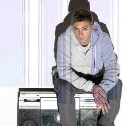 DJ Fresh sitting on a ghetto blaster