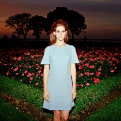 lana-del-rey-standing-in-front-of-a-flower-bed-looking-miserable